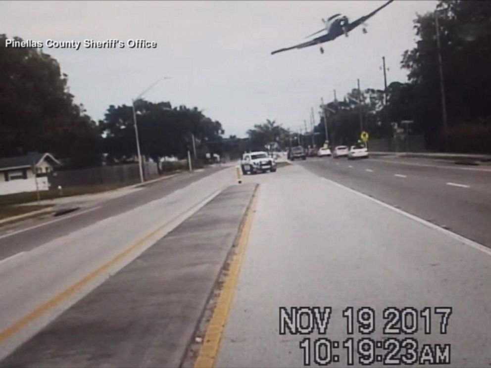PHOTO: A small plane captured on video by a sheriffs deputy squad car banks over a road before crashing in Clearwater, Fla., Nov. 19, 2017.