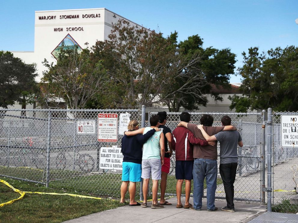 PHOTO: People look on at the Marjory Stoneman Douglas High School, Feb. 18, 2018, in Parkland, Florida.