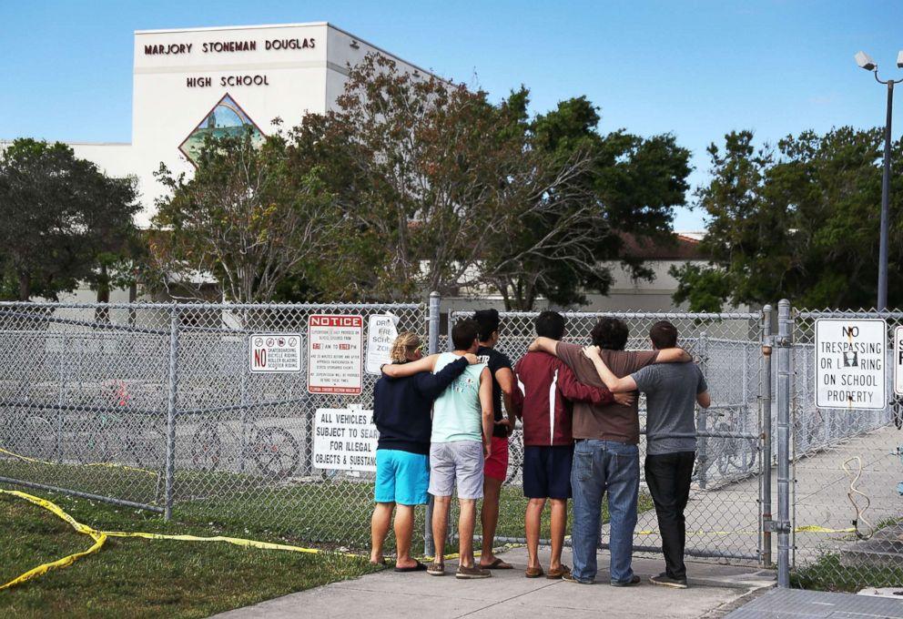 PHOTO: People look on at the Marjory Stoneman Douglas High School on Feb. 18, 2018, in Parkland, Fla.