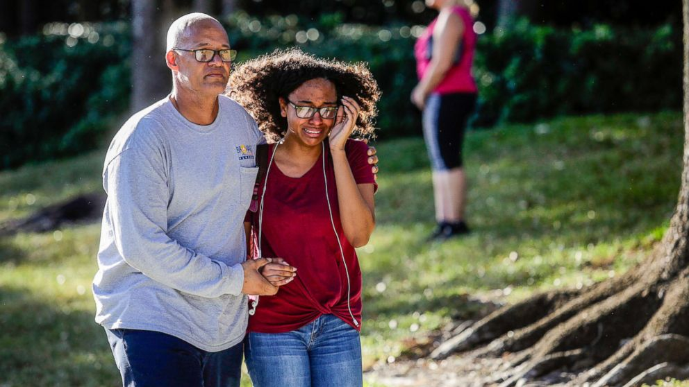 A father and daughter embrace after a mass shooting at the Marjory Stoneman Douglas High School in Parkland, Fla., Feb. 14, 2018.