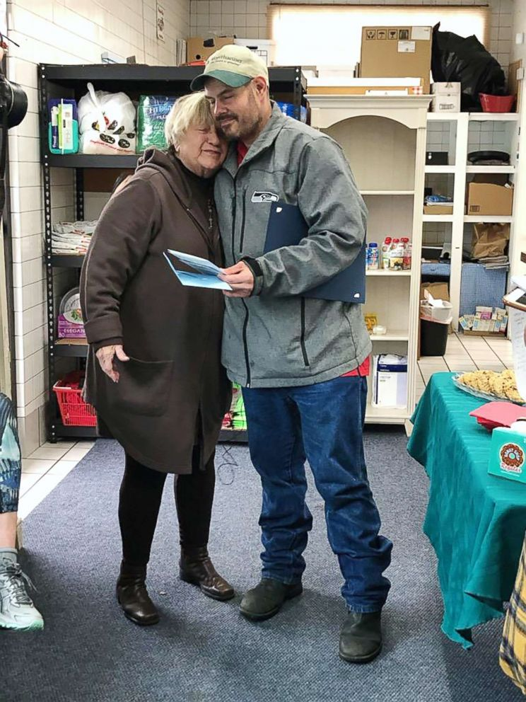 PHOTO: Kevin Booth and Anita Miller hug after Miller presented Booth with thank you cards in honor of his good deed at Sumner Community Food Bank, on Nov., 29, 2018.