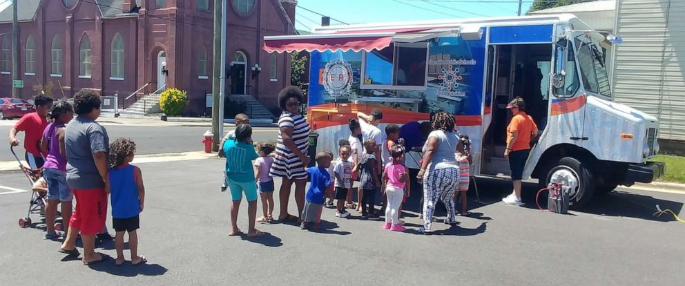 PHOTO: Students line up to a food truck providing free meals by Danville Public Schools in Virginia, June 11, 2019.