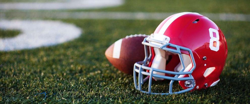 PHOTO: Football and helmet on a field.