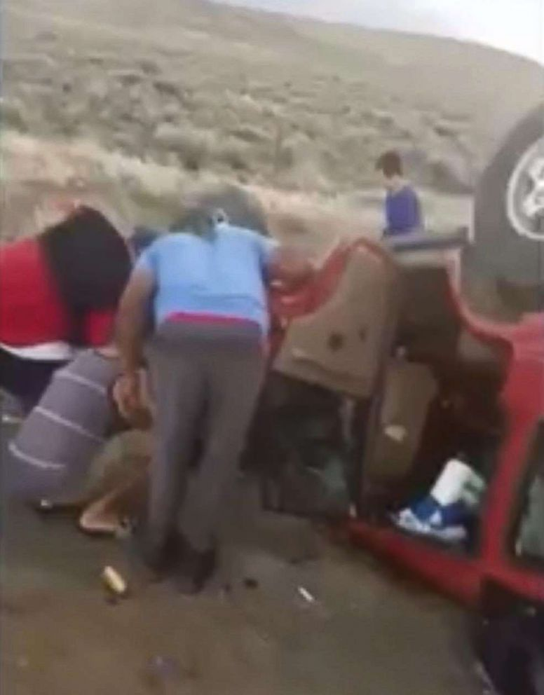 PHOTO: Members of the Boise Black Knights youth football team lift an overturned vehicle at they cut a woman out of her seat belt, May 30, 2018.