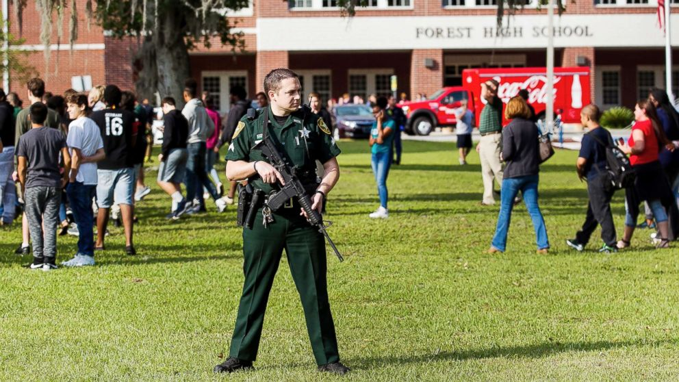 A Marion County Sheriff's Deputy stands outside Forest High School as students exit the school after a school shooting occurred on April 20, 2018 in Ocala, Fla.