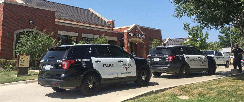 PHOTO: A Fort Worth police officer and vehicles are seen outside a Veritex Bank in Fort Worth, Texas, July 19, 2018, following a shooting which took place inside the bank.