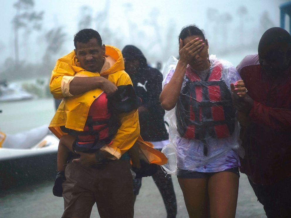 PHOTO: A family is escorted to a safe zone after they were rescued as Hurricane Dorian continues to rain in Freeport, Bahamas, Sept. 3, 2019.