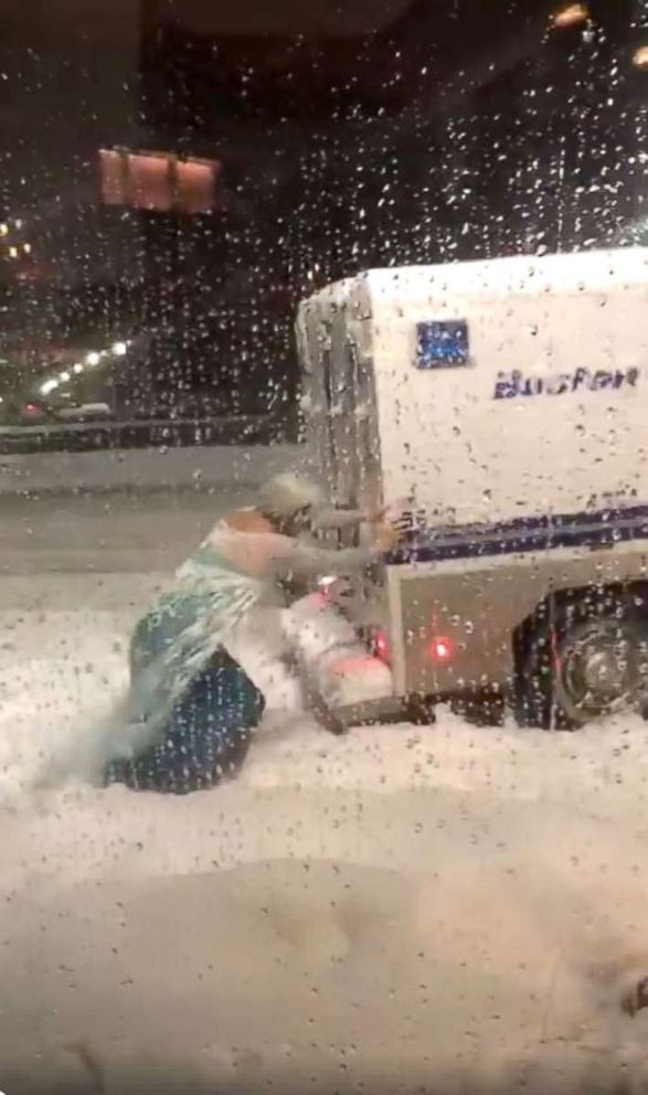 PHOTO: A man dressed as Elsa, from Frozen, helps a Boston Police vehicle that was stuck in the snow, March 13, 2018.