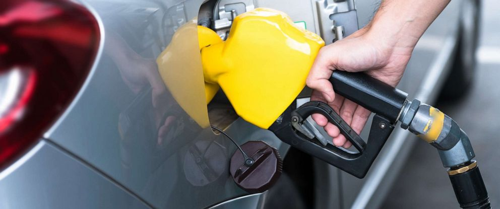 PHOTO: Hand refilling the car with fuel, close-up.