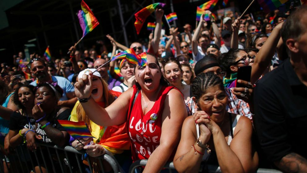Revellers standing on Seventh Avenue watch the annual Pride Parade on June 24, 2018 in New York City.