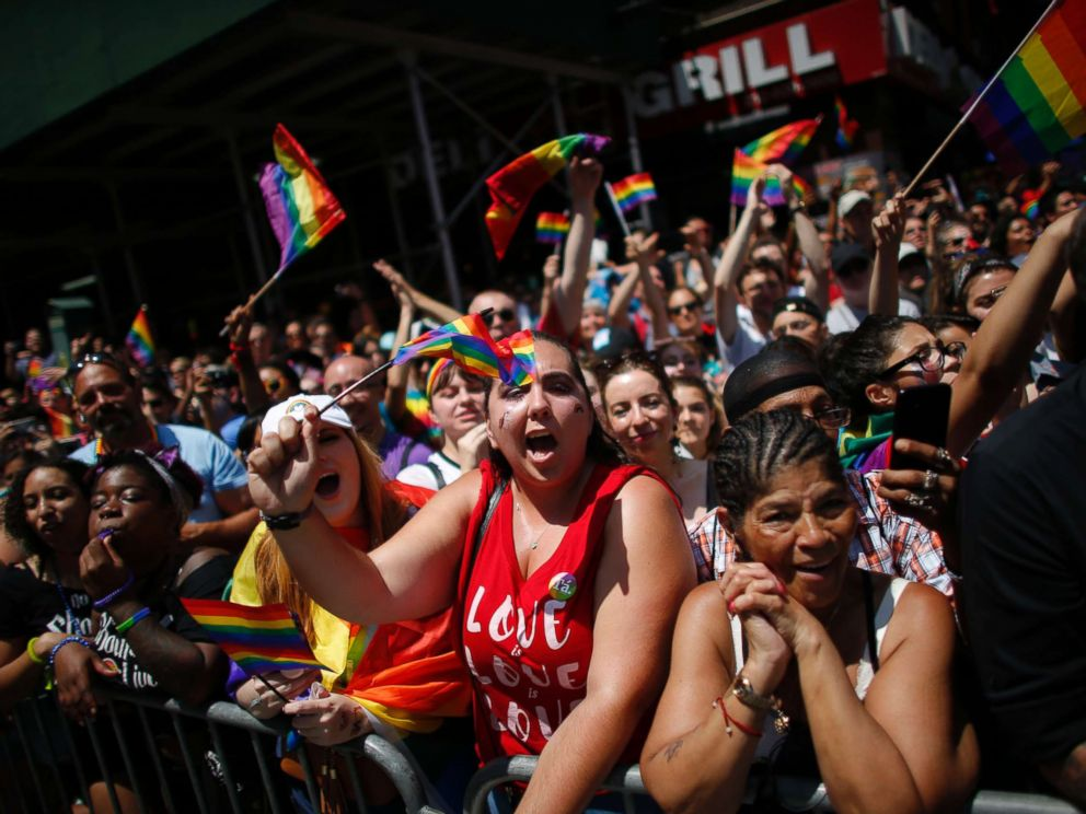 PHOTO: Revellers standing on Seventh Avenue watch the annual Pride Parade on June 24, 2018 in New York City.