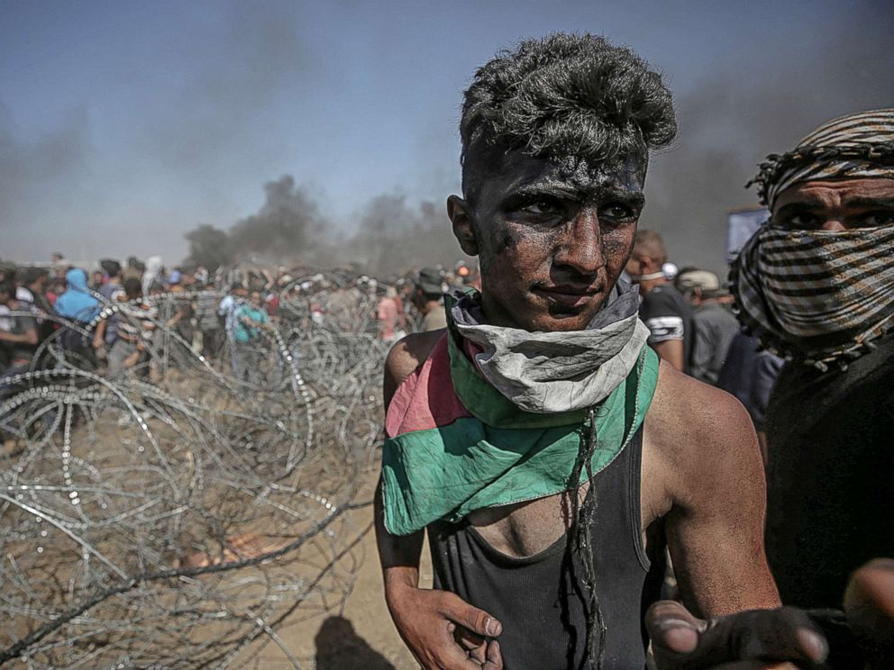 PHOTO: Palestinians protesters pull barbed wire fence installed by Israeli army along the border during clashes after protests near the border with Israel in the east of Gaza Strip, May 14, 2018.