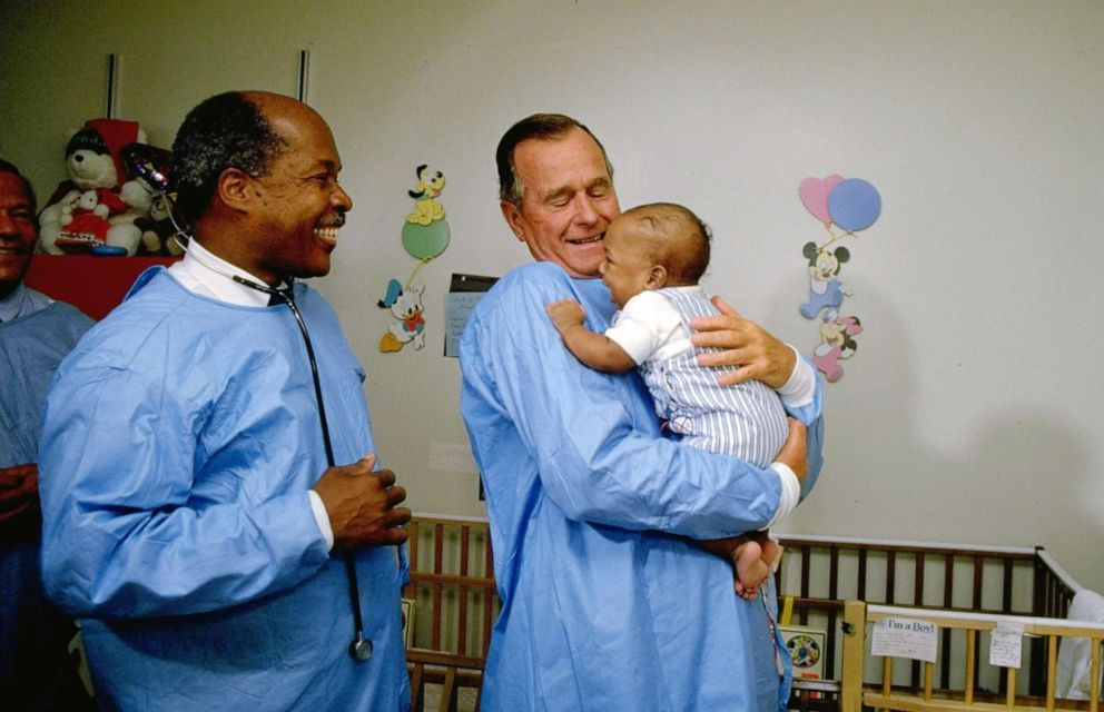 PHOTO: President George H.W. Bush holds a baby that was diagnosed with AIDS while the Secretary of Health and Human Services, Louis Sullivan, looks on, in 1989.