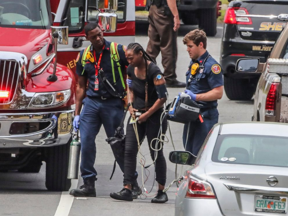PHOTO: Henry County paramedics examine a woman near a scene after a gunman reportedly shot a few Henry County police officers in Stockbridge, Ga., Thursday, April 4, 2019.
