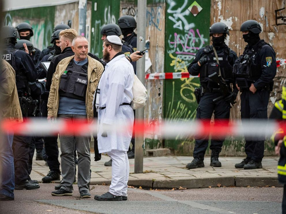 PHOTO: Rescued parishioners of the Jewish community and police forces stand near the scene of a shooting that has left two people dead on Oct. 9, 2019 in Halle, Germany.