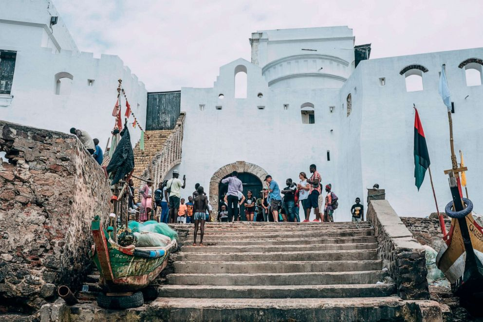 "PHOTO: Visitors gather on August 18, 2019, at Cape Coast Castle, in Ghana, outside the ""Door of No Return"", through which enslaved Africans were loaded as cargo onto the ships that took them across the Atlantic to the Americas."