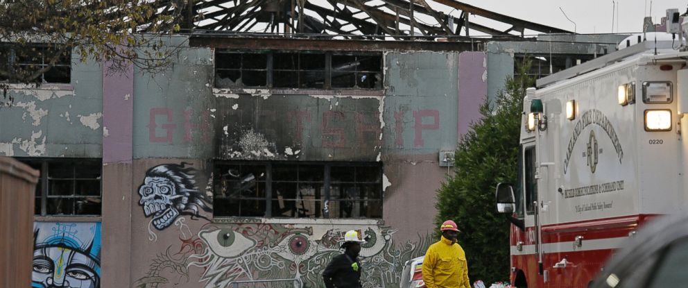 In this Dec. 7, 2016 file photo, Oakland fire officials walk past the remains of the Ghost Ship warehouse damaged from a deadly fire in Oakland, Calif.