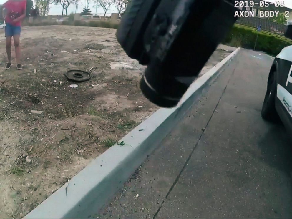PHOTO: This photo made from a May 3, 2019 police video camera video released by the Oxnard, Calif., Police Department shows a 17-year-old girl reaching to her pocket in front of an officer with a gun, partly seen top front, in Oxnard.