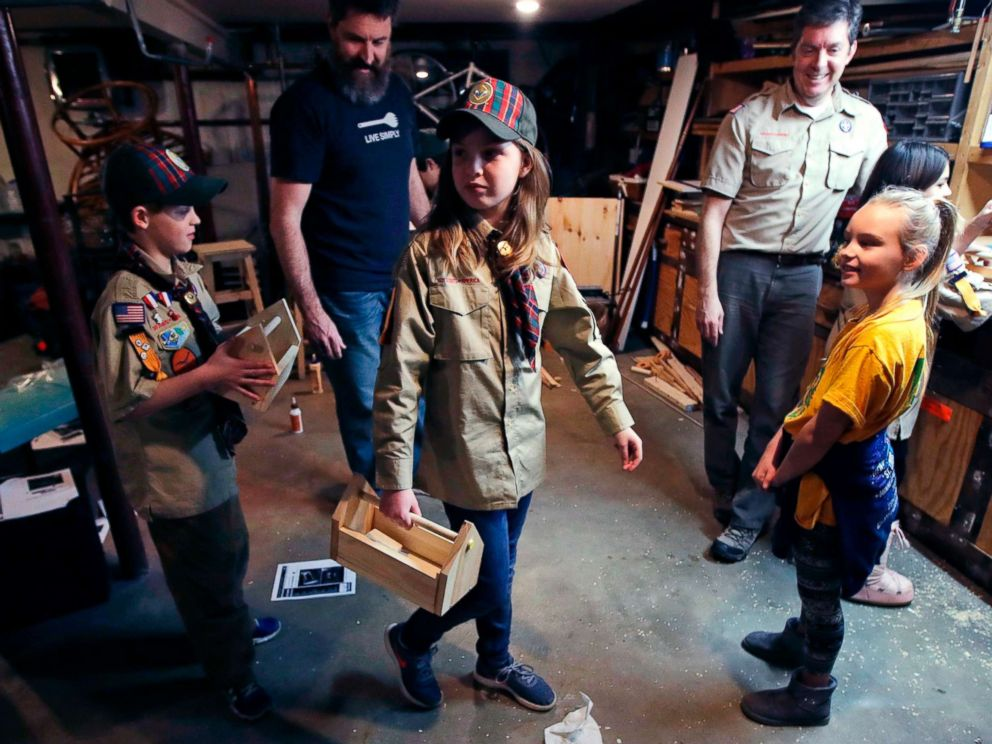 PHOTO: Tatum Weir, center, carries a tool box she built as her twin brother Ian, left, follows after a Cub Scout meeting in Madbury, N.H., March 1, 2018.