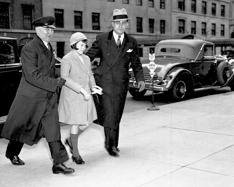 PHOTO:Assisted by chauffeur, Gloria Vanderbilt returns to mothers home after attending Palm Sunday services at Church of St. Francis of Assisi, April 14, 1935.
