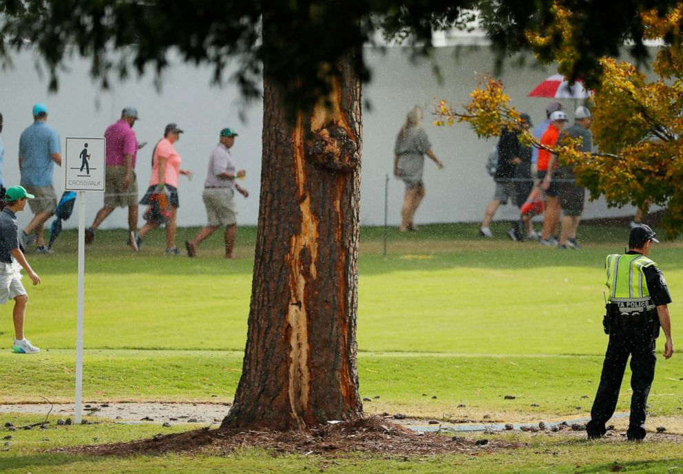 PHOTO: Fans walk past lightning damage to a tree during a suspension in play due to inclement weather during the third round of the TOUR Championship at East Lake Golf Club on August 24, 2019 in Atlanta, Georgia.