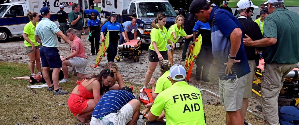 PHOTO: Fans are assisted by medical personnel after a lightning strike during the third round of the Tour Championship golf tournament at East Lake Golf Club.