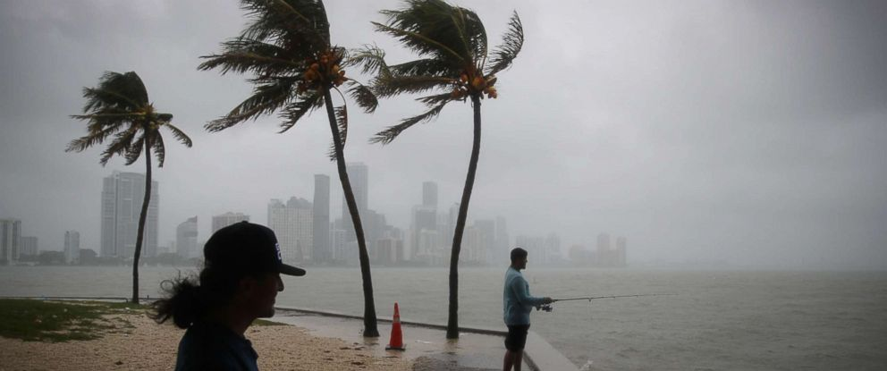 PHOTO: Walter Augier (L) and Jhon M. fish as rain and wind are whipped up by Tropical Storm Gordon, Sept. 3, 2018 in Miami.