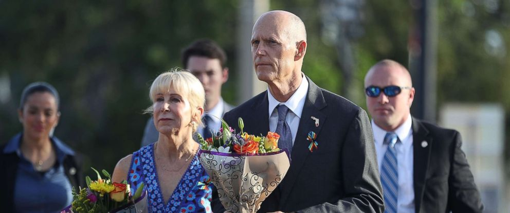 PHOTO: Florida Governor Rick Scott and First Lady Ann Scott carry flowers as they visit the memorial to the 49 shooting victims setup at the Pulse nightclub where the shootings took place two years ago, June 12, 2018, in Orlando, Fla.