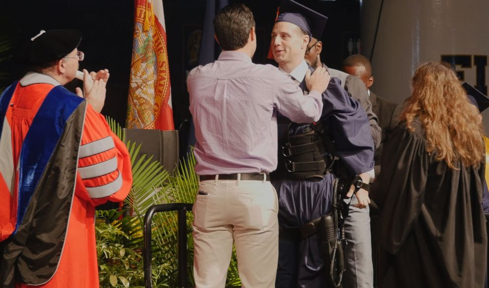 PHOTO: Aldo Amenta used an exoskeleton to walk across the stage to get his diploma at Florida International University.