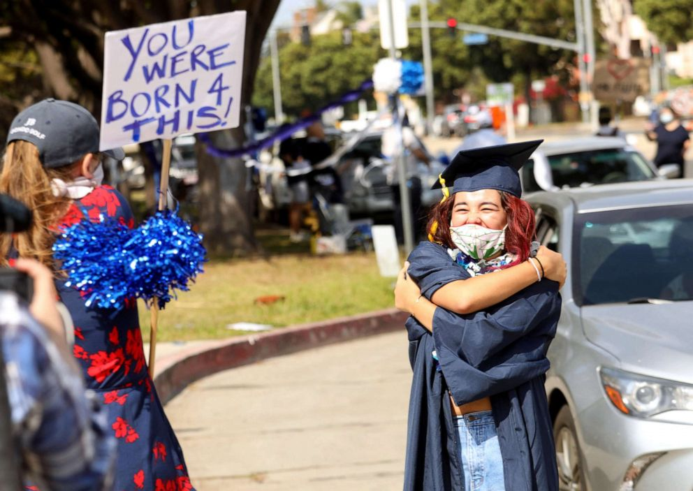 PHOTO: Venice High School graduate Hiromi Maeda, 18, gives her teacher a socially distant hug while arriving at the Venice High School Class of 2020 Senior Graduation Parade in Venice, Calif., June 12, 2020.