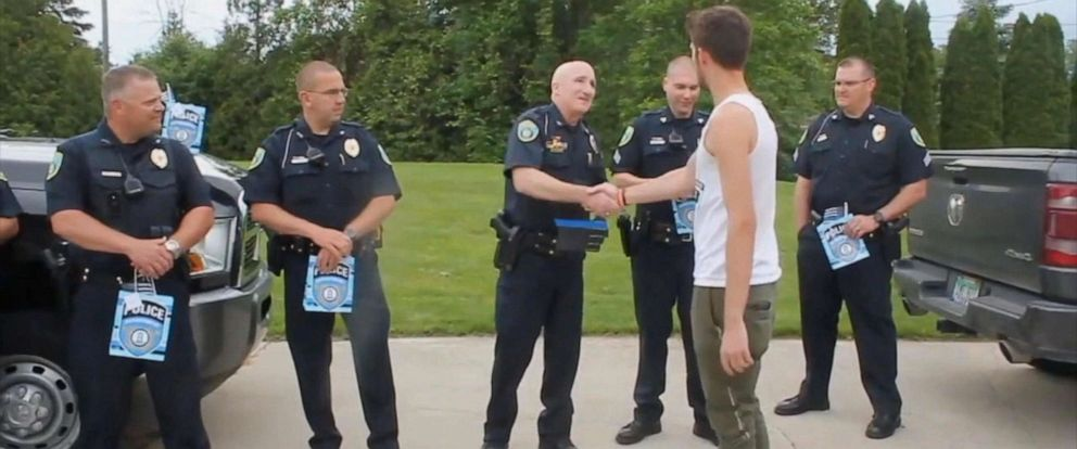 PHOTO: Micah Schieber shakes hands with police officers who showed up for his high school graduation in Midland, Michigan, in honor of his father, former police officer Chad Schieber, who died when Micah was just 6-years-old.
