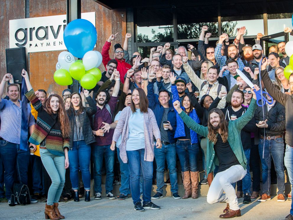 PHOTO: Dan Price, in the green shirt, CEO of Gravity Payments, celebrates the opening of Gravity Payments new Boise office. Price said he expects to add more workers over time. (Katherine Jones/Idaho Statesman/Tribune News Service via Getty Images)