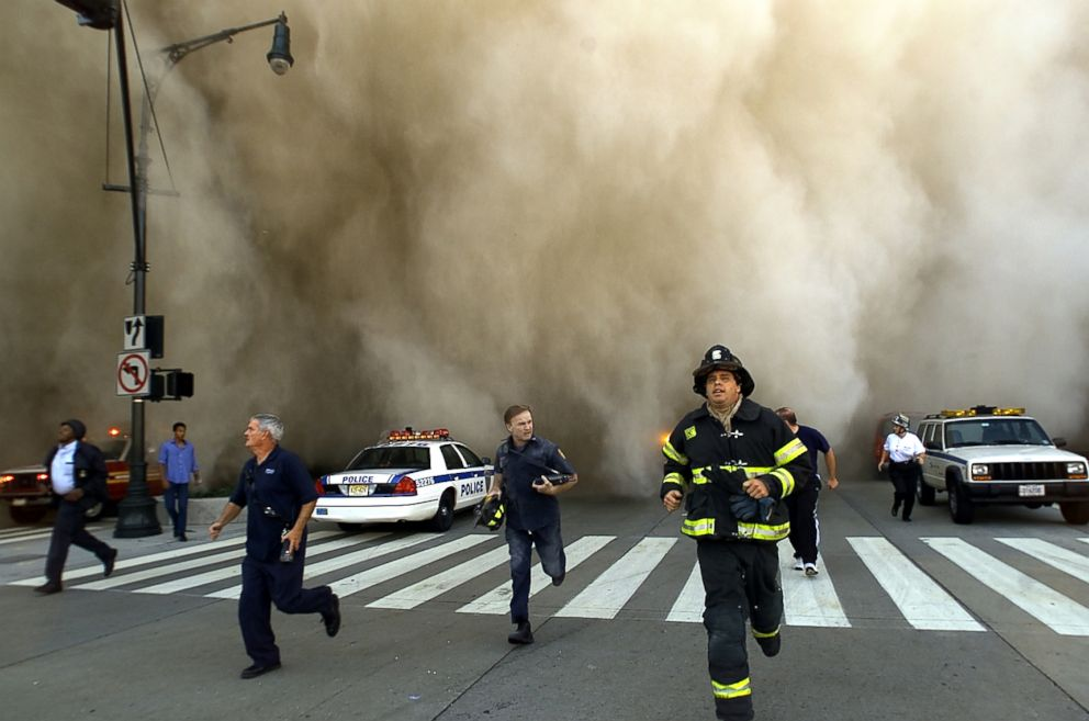 PHOTO: Policemen and firemen run away from the huge dust cloud caused as the World Trade Centers Tower One collapses after terrorists crashed two hijacked planes into the twin towers, Sept. 11, 2001 in New York City.