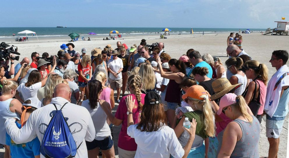 PHOTO: A group of supporters gathered with Stephanie Young McCluney, wife of Brian McCluney, one of two missing boaters, at Jetty Park, Port Canaveral, Fla., Aug. 18, 2019, to pray and search the shore for clues.