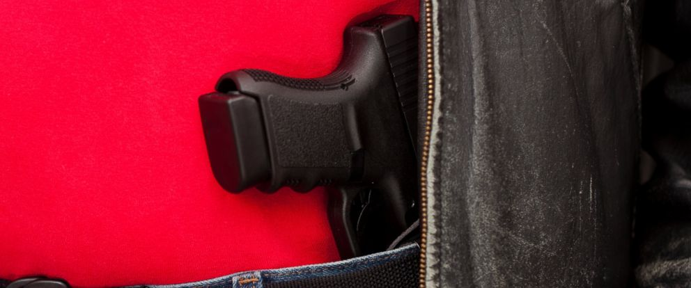 PHOTO: A semiautomatic pistol is pictured in a holster under a leather jacket in an undated stock photo.