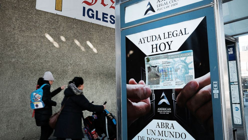 A sign at a bus stop advertises immigration services in a neighborhood of the Queens borough of New York City with a large Latino immigrant population on Feb. 14, 2017.