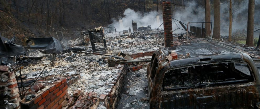 PHOTO: The remains of a home smolder in the wake of a wildfire, Nov. 30, 2016, in Gatlinburg, Tennessee.