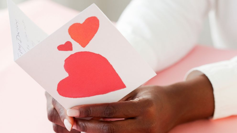 A woman holds a Valentine card in an undated stock photo.