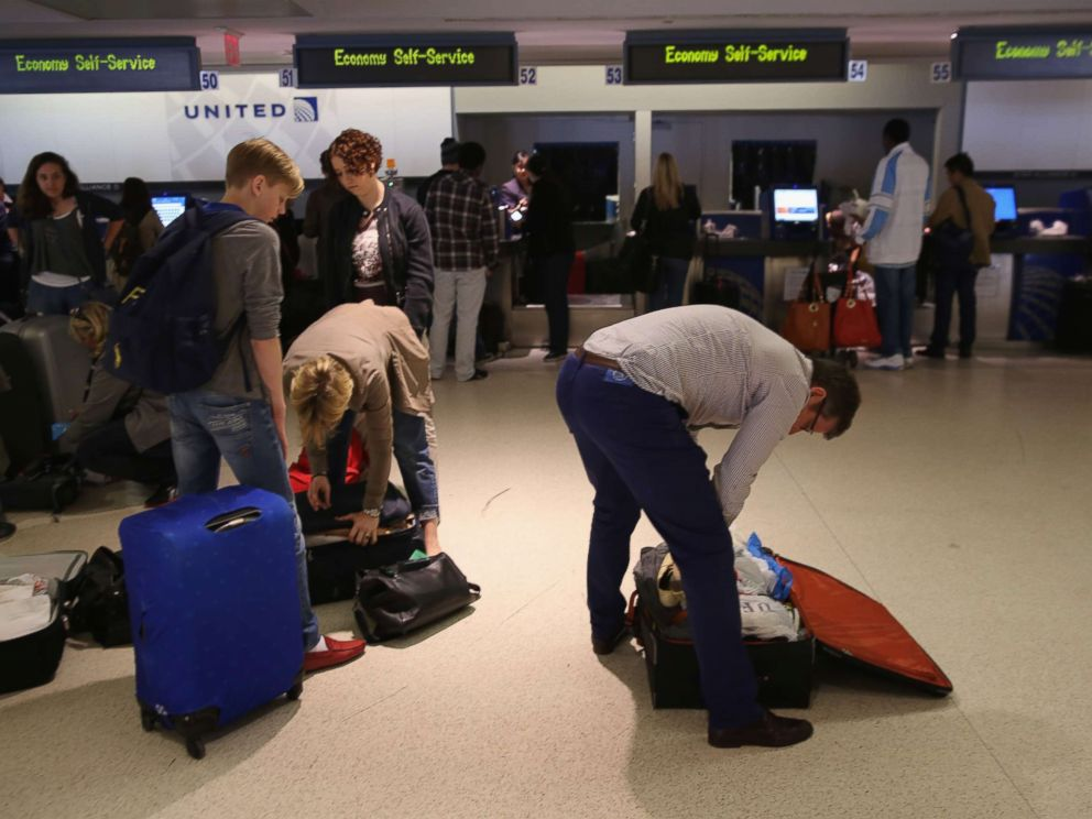 Passengers repack luggage before it is screened at a new explosives detection system at the Newark Liberty International Airport on May 1, 2014.