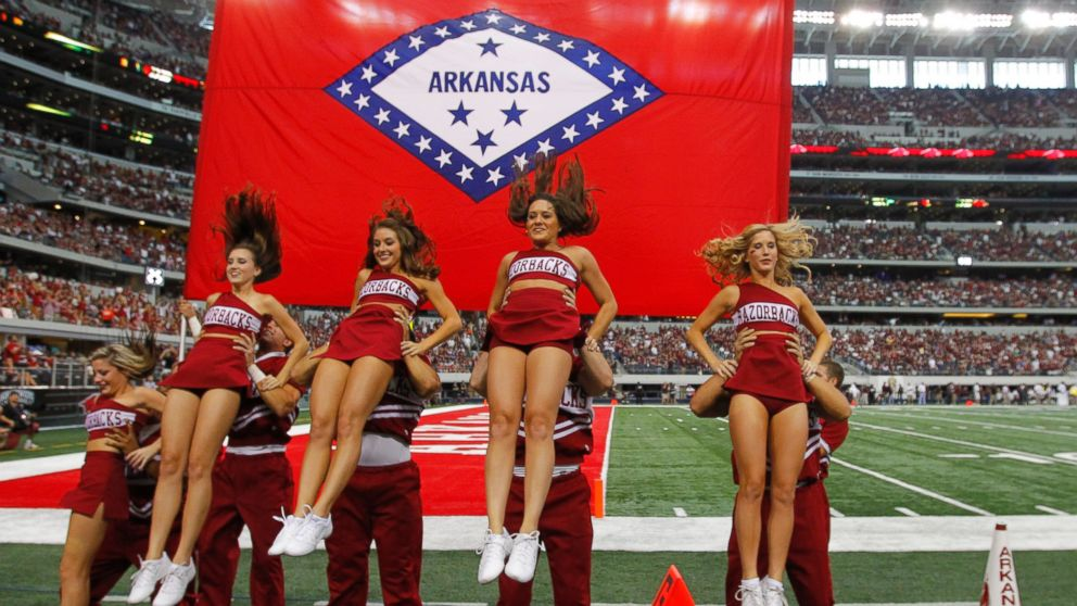 Arkansas cheerleaders perform a routine in front of their state flag at Cowboys Stadium in Arlington, Texas, on Oct. 1, 2011.