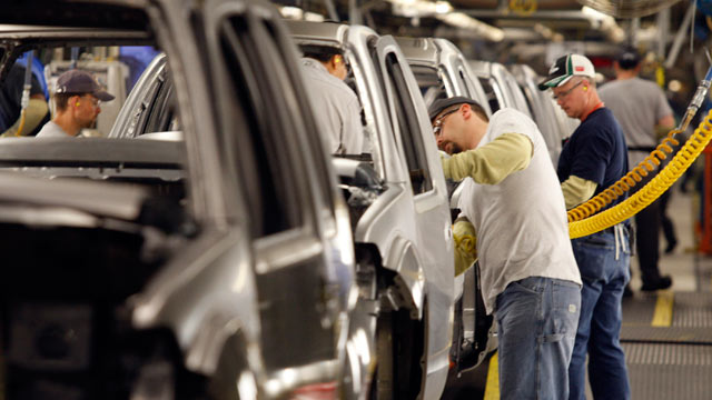 PHOTO: Employees work on vehicles on the assembly line for a company plant.