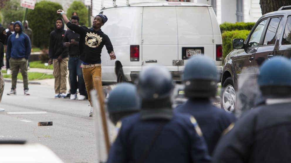 A protester throws a rock at police during riots in Baltimore, USA on April 27, 2015.