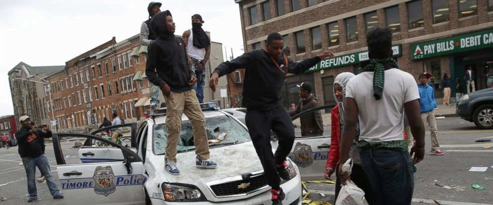 Demonstrators climb on a destroyed Baltimore Police car in the street during violent protests following the funeral of Freddie Gray, April 27, 2015 in Baltimore.