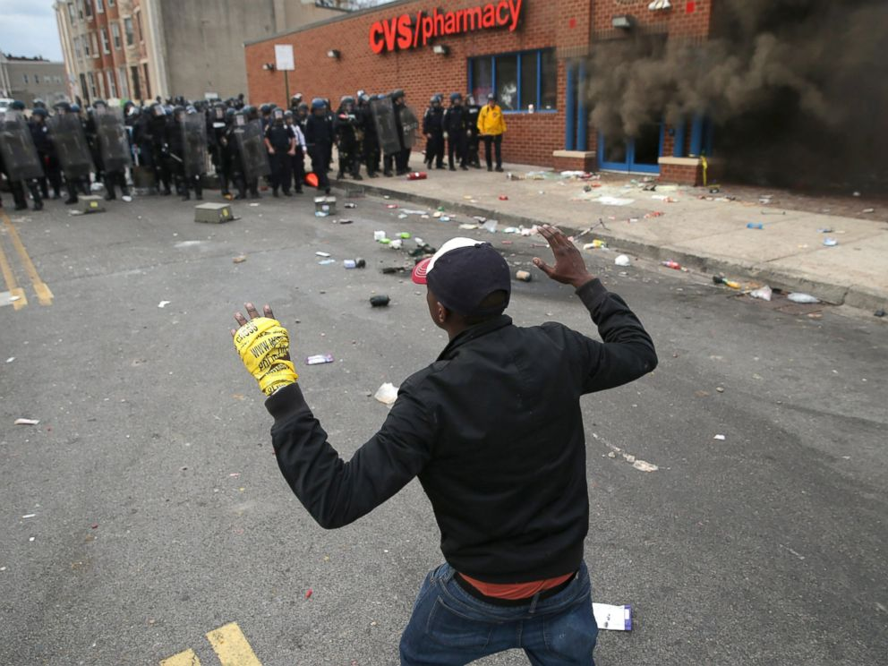 PHOTO: A man faces down a line of Baltimore Police as a CVS burns during violent protests following the funeral of Freddie Gray, April 27, 2015 in Baltimore.