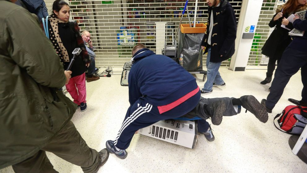Customers fall to the floor as they grapple for an LED television during a Black Friday discount sale at an Asda supermarket in London on Nov. 28, 2014.