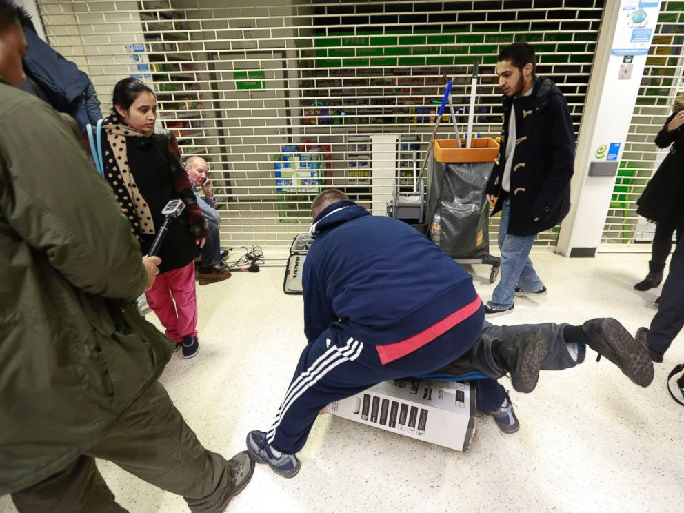 PHOTO: Customers fall to the floor as they grapple for an LED television during a Black Friday discount sale at an Asda supermarket in London on Nov. 28, 2014.