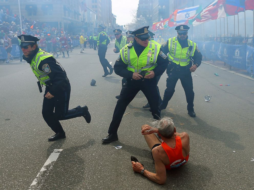 PHOTO: A runner is on the ground as police officers draw their guns after the second explosion near the finish line of the 117th Boston Marathon, April 15, 2013.