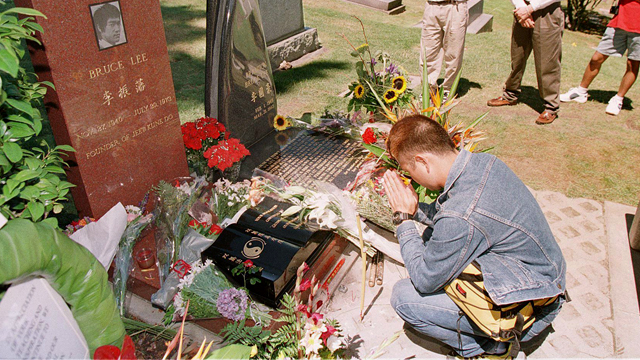 PHOTO: Yuki Shigeoka of Tokyo sits by the gravesite of martial arts leader and movie star Bruce Lee at a cemetery in Seattle, Wash. on the day of the 25th anniversary of Lee's death July 20, 1998.
