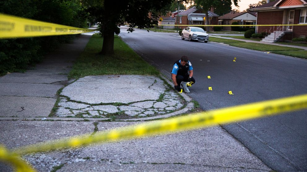 A member of the Chicago Police Department collects bullet casings at the scene of a shooting near the intersection of South Morgan Street and West 97th Street in Chicago on July 3, 2016.