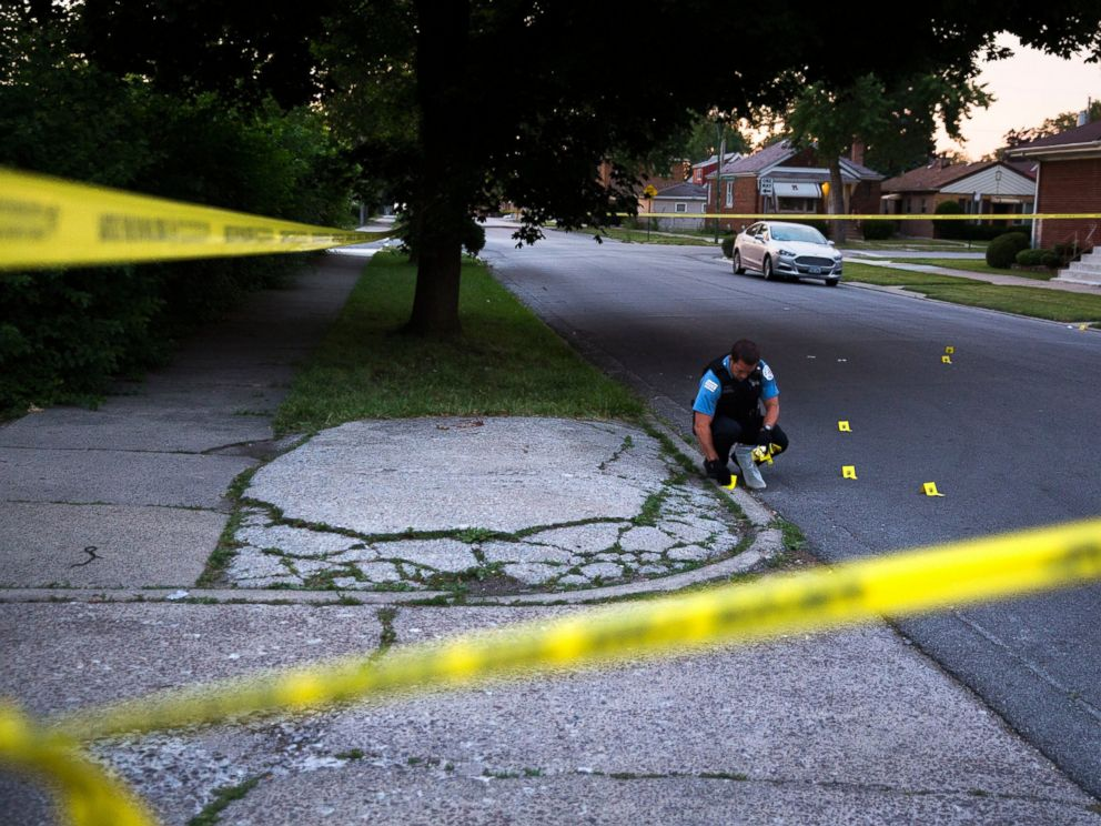 PHOTO: A member of the Chicago Police Department collects bullet casings at the scene of a shooting near the intersection of South Morgan Street and West 97th Street in Chicago on July 3, 2016.